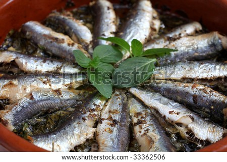 Fresh sardines baked with parsley, olive oil, oregano, pepper, salt and lemon juice in a terracotta bowl, topped with sprigs of mint