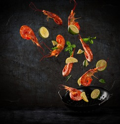 Fresh sea food flying into a pan on dark background