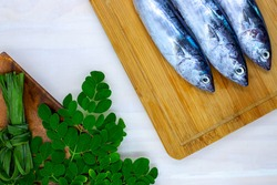 Fresh sea mackerel and greenery on white wooden background, sea food cooking top view photo. Raw fish with moringa leaf. Philippine cuisine meat herb. Healthy fish dish ingredient. Recipe book banner