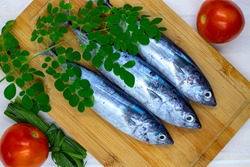 Fresh sea sardine and greenery on white wooden background, sea food cooking top view photo