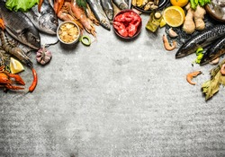 Fresh seafood. Different fish, shrimp and shellfish with slices of lemon and spices. On a stone background.