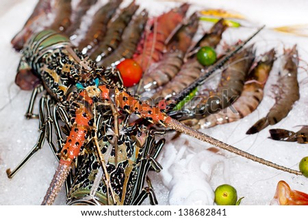 Fresh seafood in asian market, lobsters prawns and fish.