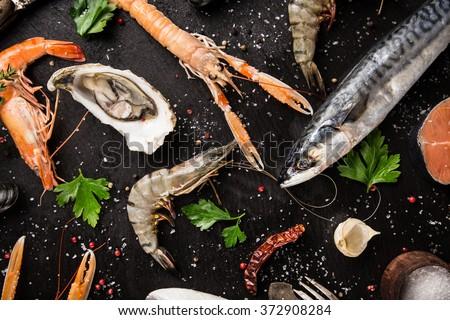 Fresh seafood on black stone, close-up. #372908284