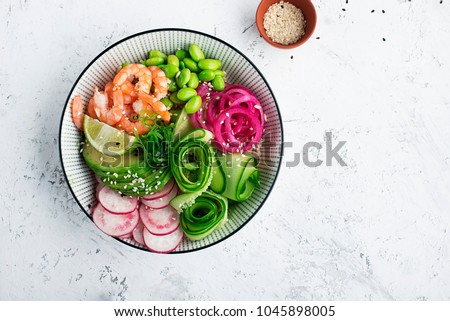 Fresh seafood recipe. Shrimp poke bowl with fresh prawn, brown rice, cucumber, pickled sweet onion, radish, soy beans edamame portioned with black and white sesame. Food concept poke bowl