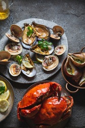 Fresh seafood shellfish mussels, clams, crabs and snails on gray background