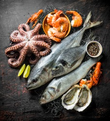 Fresh seafood with spices and lime slices. On dark rustic background