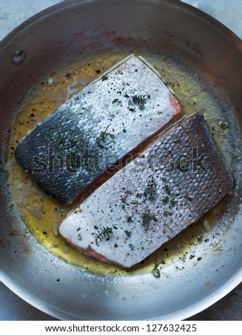 Fresh seasoned salmon fillets cooking in stainless saute pan