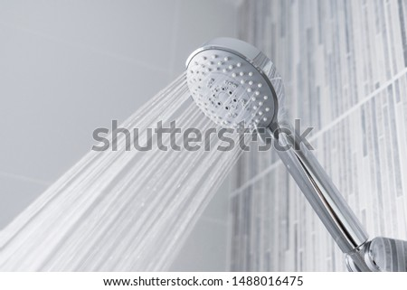 Fresh shower behind wet glass window with water drops splashing. Water running from shower head and faucet in modern bathroom. Foto stock ©