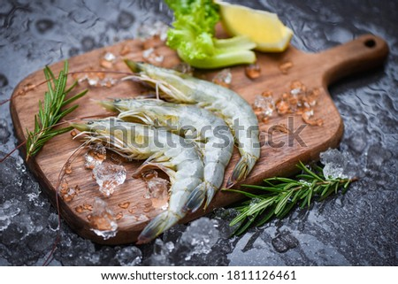 fresh shrimp on wooden cutting board with rosemary ingredients herb and spices for cooking seafood  raw shrimps prawns on ice frozen at the seafood restaurant