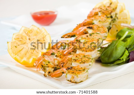 Fresh shrimp skewers on a white plate with citrus, salad and seafood sauce. Shallow depth of field.