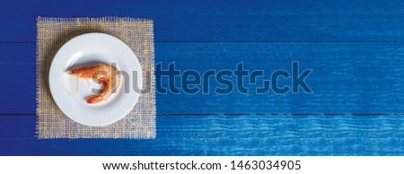 Fresh shrimp website banner on white plate with navy blue background Stock fotó ©