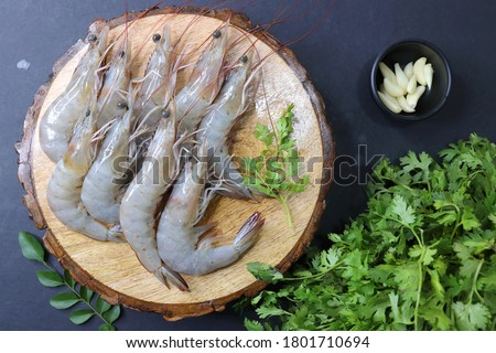 fresh shrimps or white prawns raw on wooden chopping board with coriander and curry leaves. on background with copy space. Stockfoto ©
