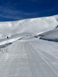 Fresh ski trail, corduroy. Ski resort in the north of Montenegro, Kolasin. Great slope for freeriding, skiing, no people. Against the background of a bright blue sky. Winer, snow mountain.