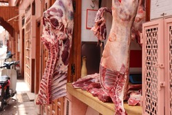 Fresh slaughtered food meat specialty to eat, hanging in shop for sale from traditional moroccan butcher at local african souk street market in arabic medina of oriental Marrakech, Morocco, Africa.