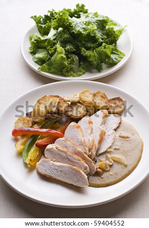 Fresh sliced chicken with roasted potato and pepper close up