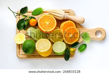 Fresh sliced citrus fruits on cutting board with wooden squeezer
