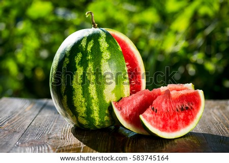 Fresh sliced watermelon wooden background,Ripe striped watermelon,Close-up of fresh slices of red watermelon,sweet harvest. Watermelon pattern. Watermelon background.