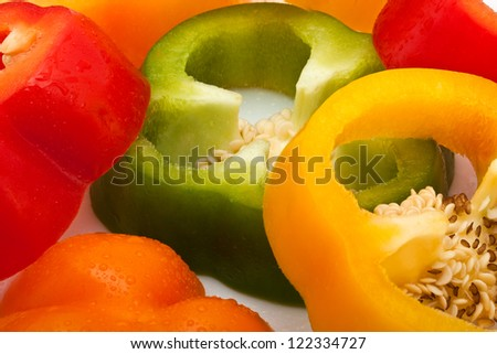 fresh slices of red, green, yellow and orange pepper with water drops isolated on white background - stock photo