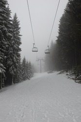 Fresh snow falling on an empty ski lift in a snowy winter landscape, with snow covered mountains and big pine and fir trees, in the fog. The chairlift has no people on it.