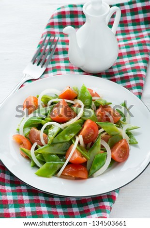 Fresh snow peas and tomato salad on plate, vertical