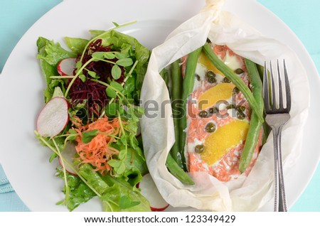 Fresh sockeye salmon poached in parchment with lemon, capers, green beans and salad greens