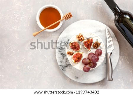 Fresh soft brie cheese with honey, walnuts, figs, grapes and bottle of red wine. Top view, close-up on gray concrete background.