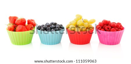 Fresh soft summer fruit in colorful cups