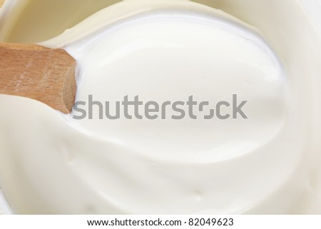fresh sour cream in a wooden spoon