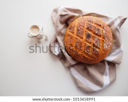 Fresh sourdough starter and homemade bread on white background