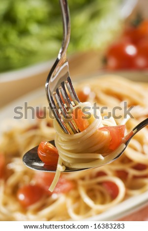 fresh spaghetti on fork and spoon close up shoot