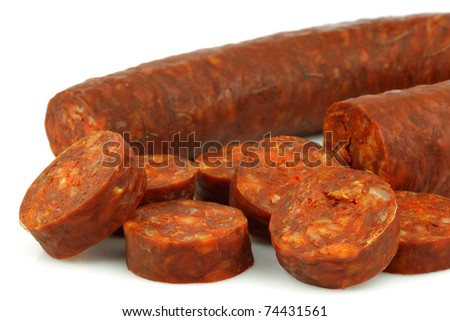 fresh Spanish chorizo sausage with some cut pieces on a white background - stock photo