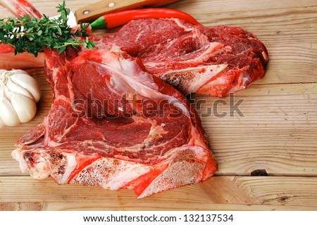 fresh spare ribs : raw lamb with thyme , garlic and red chili pepper on wooden board