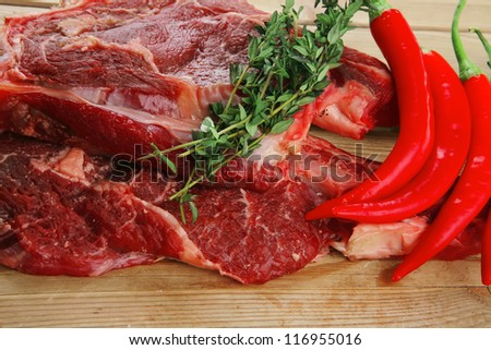 fresh spare ribs : raw lamb with thyme , red chili pepper , and green onion on wooden board