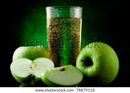 Fresh sparkling green apple juice on green spot lighted background