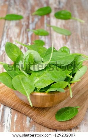 Fresh spinach in a wooden bowl on the table, vertical