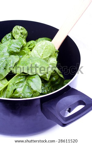 Fresh spinach leaves being prepared in a cooking pot