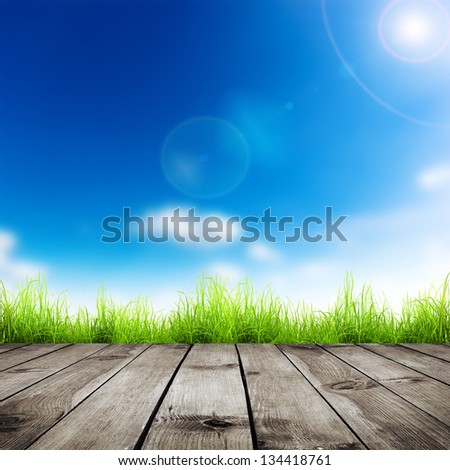 Fresh spring green grass with blue bokeh and sunlight and wood floor Natural background