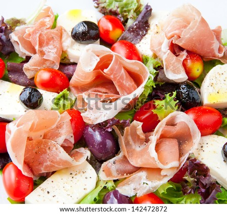 Fresh spring mix salad italian style with prosciutto and mozzarella, seasoned with olive oil and black pepper.
