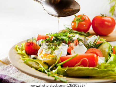 Fresh spring salad with pouched egg and vegetable oil