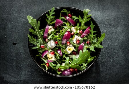 Fresh spring salad with rucola, feta cheese, red onion and pomegranate seeds in black bowl on chalkboard background.  #185678162