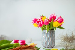 Fresh spring yellow and pink tulips bouquet in a vase, other flowers and details on florist workspace on white wooden table. Education of floristry. Selective focus. Copy space