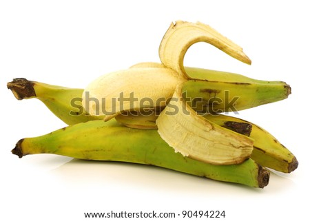 fresh still unripe plantain (baking) banana and a peeled one on a white background
