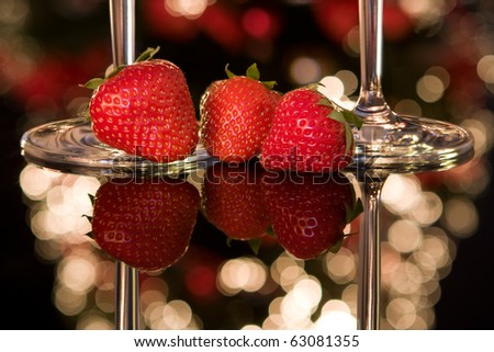 Fresh strawberries and champagne glasses in front of a blurred christmas tree