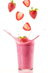Fresh strawberries falling into a glass to make a delicious strawberry smoothie. White background.