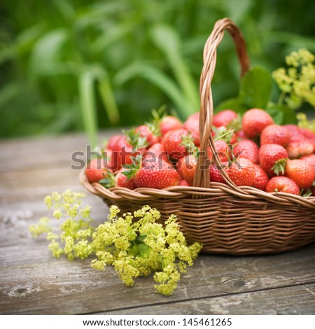 Fresh strawberries in a basket on old wooden table, selective focus