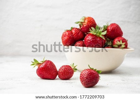 Fresh strawberries in a bowl on marble white table. Fresh nice strawberries. Strawberry field on fruit farm. Heap of Red strewberry on plate close up. Juice strawberry. Strawberry field on fruit farm.
