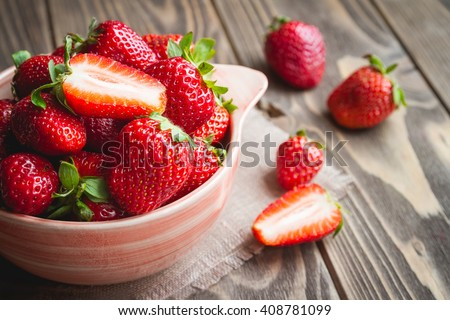 Fresh strawberries in a bowl on wooden table with low key scene.