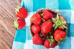 fresh strawberries in a bowl with checkered napkin on old wooden background