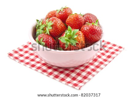 Fresh strawberries in a pink bowl isolated over white