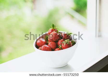 fresh strawberries in a white bowl on a window